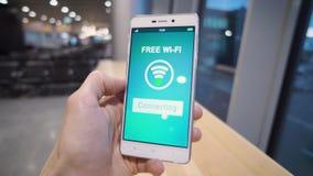 Smart Phone della tenuta della mano con il segno libero di wifi sullo schermo sopra il fondo della sfuocatura, l'affare ed il con video d archivio