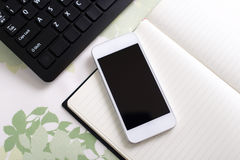 Smart phone on the desk. Personal computer keyboard with smart phone stock photography