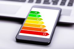 Close-up Of Mobile Phone With Energy Efficiency Chart On Screen. Close-up Of Laptop And Mobile Phone With Energy Efficiency Chart On Screen Over Desk royalty free stock images