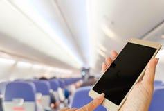 Smart Phone di uso della mano dentro l'aeroplano fotografia stock libera da diritti