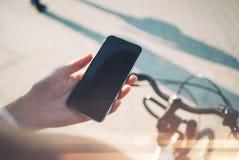 Smart Phone e bicicletta che viaggiano nella città Immagine Stock