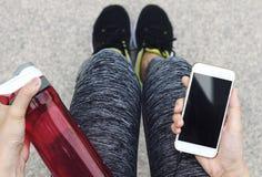 Smart Phone e bottiglia di acqua femminili della tenuta del corridore immagini stock libere da diritti