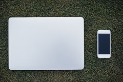 Smart Phone e computer portatile su erba verde Immagine Stock