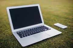 Smart Phone e computer portatile su erba verde Fotografia Stock