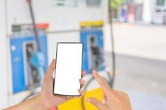 Smart Phone e stazione di servizio della tenuta della mano nel fondo Immagine Stock