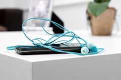 Smart phone with earphones on the table Royalty Free Stock Image