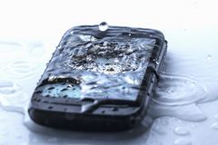 Smart phone fail broken on tile floor with water spilled Stock Photos