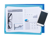Smart phone and financial reports Royalty Free Stock Image