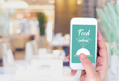 Smart phone with food online device on screen over blur restaura. Hand holding smart phone with food online device on screen over blur restaurant background Royalty Free Stock Photos
