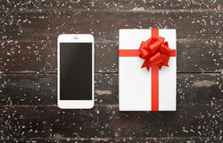Smart phone and gift with bow on wooden table Royalty Free Stock Images