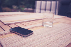 Smart phone and glass on table Royalty Free Stock Images