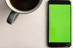 Smart phone with green screen next to coffee cup. Smart phone with green screen on display next to coffee cup Royalty Free Stock Photography