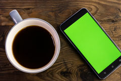 Smart phone with green screen next to coffee cup. Smart phone with green screen on display next to coffee cup, distressed wood table Royalty Free Stock Images