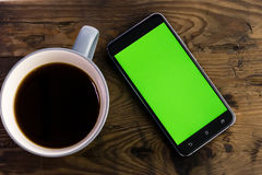 Smart phone with green screen next to coffee cup. Smart phone with green screen on display next to coffee cup, distressed wood table Stock Photography