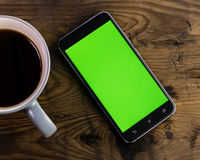 Smart phone with green screen next to coffee cup. Smart phone with green screen on display next to coffee cup, distressed wood table Royalty Free Stock Photos