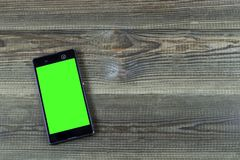 Smart phone with green screen on wooden desk