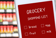 Smart phone with grocery online shopping list on screen over blu Royalty Free Stock Photo