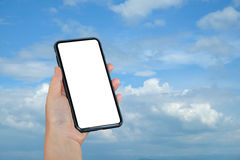 Smart phone in hand on blue sky background. Stock Photos
