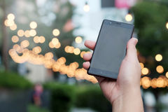 Smart phone in hand with bokeh in park background. And have some space for write wording Royalty Free Stock Images