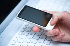 Smart phone in hand  with laptop Royalty Free Stock Images