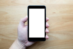 Smart phone on hand. Smart phone on man hand show white screen with wooden background royalty free stock photo