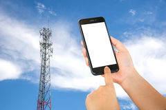 Smart phone in hand with mobile towers background. Stock Photos