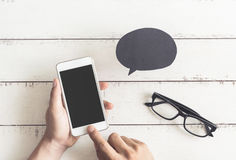 Smart phone with hand touching screen and talk bubbles Stock Photo