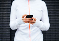 Smart phone in hands of young woman. Closeup of young woman taking a break form workout using mobile phone. Focus on hands and smart phone royalty free stock photo