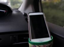 Smart phone hang on cup holder inside car front selective focus royalty free stock images
