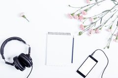 Smart phone, headphones, paper notepad, pencil and flowers lie o Stock Photo