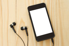 Smart phone with headphones on wooden background royalty free stock image