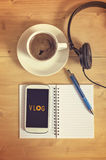 Smart phone with headset, notebook, pencil, coffe cup on wooden table. Royalty Free Stock Image