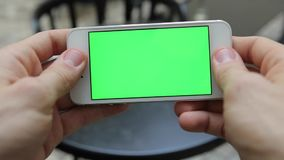 Smart Phone Held by Hand. Green screen Chroma Key. Tracking Motion Vertical. Person Sitting Telephone on the Hands Rotate Animation stock video