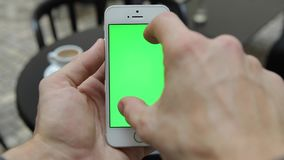 Smart Phone Held by Hand. Green screen Chroma Key. Tracking Motion Vertical. Person Sitting Telephone on the Hand Swipe Down-Up Animation stock footage