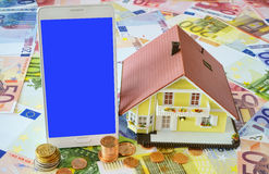 Smart phone and Home Ownership. Smart phone with blank display and a model of a Home Ownership on a background made of Euro banknotes and coins Stock Images