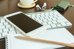 Smart phone on keyboard and notepad with pencil Royalty Free Stock Photography
