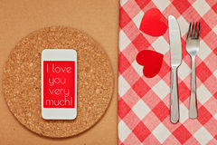 Smart phone on the kitchen table with fork and knife for a declaration of love. Stock Photography