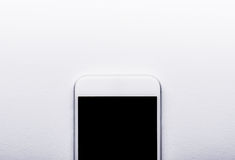 Smart phone laid on white office desk, copy space Royalty Free Stock Photos