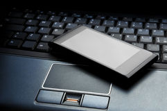 Smart phone on laptop Stock Images