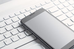 Smart phone on the laptop Stock Photo