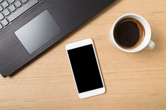 Smart phone, laptop and cup of coffee on work table Stock Image