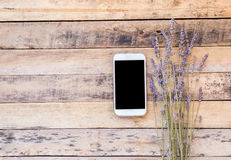 Smart phone and lavender flower on old wooden table background. Royalty Free Stock Photos