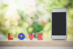 Smart phone and love alphabet on wood Royalty Free Stock Images