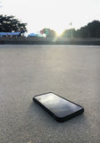 Smart phone lying on a sand of the clear beach with as light of sunset, it's mean stop social for relax Stock Image