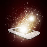 Smart phone with magic light and falling stars Stock Photo