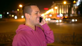 Smart phone man calling on mobile phone at night in city. Handsome young business man talking on smartphone smiling. Smart phone man calling on mobile phone at stock video footage