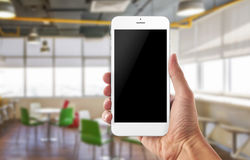 Smart phone in man hand. Office background. Blank screen for app promotion Stock Photo