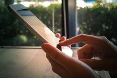 Smart Phone mobile della tenuta della mano della donna alla caffetteria, un iphone fotografia stock