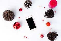 Smart phone mobile display on table with isolated white screen for mockup in Christmas time. cones and decorations in background. royalty free stock image