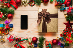 Smart phone mock up and gift box with Christmas decorations Royalty Free Stock Photo